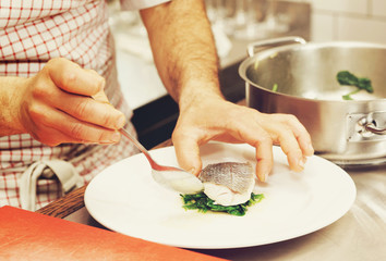 Chef is serving boiled seabass, toned