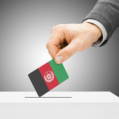 Voting concept - Male inserting flag into ballot box - Afghanist