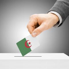 Voting concept - Male inserting flag into ballot box - Algeria