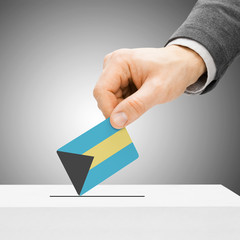 Voting concept - Male inserting flag into ballot box - Bahamas