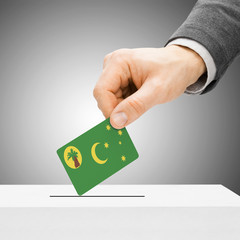 Voting concept - Male inserting flag into ballot box - Cocos (Ke