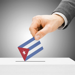 Voting concept - Male inserting flag into ballot box - Cuba