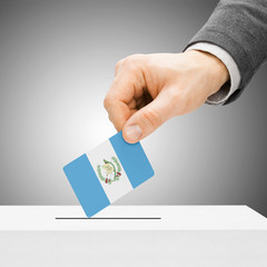 Voting concept - Male inserting flag into ballot box - Guatemala