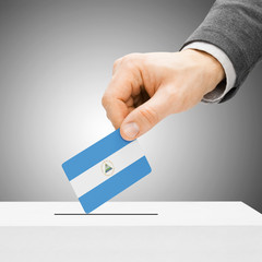 Voting concept - Male inserting flag into ballot box - Nicaragua