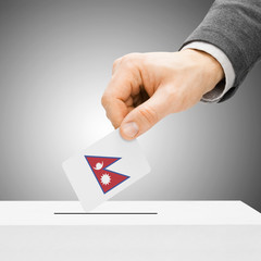 Voting concept - Male inserting flag into ballot box - Nepal