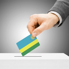 Voting concept - Male inserting flag into ballot box - Rwanda