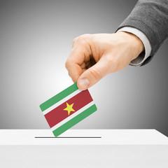 Voting concept - Male inserting flag into ballot box - Suriname