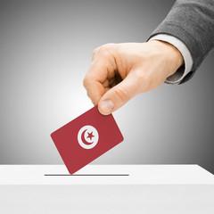 Voting concept - Male inserting flag into ballot box - Tunisia