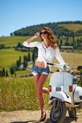 Young beautiful italian woman sitting on a italian scooter in tu
