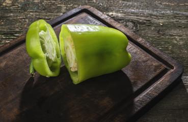 Cut green pepper on wood