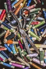 Old vintage scissors on spools of thread