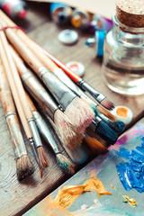 Vintage stylized photo of paintbrushes closeup, artist palette a