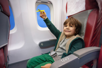 Little boy play with toy plane flying to vacation