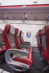 Row of red sits in airplane and window