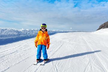 Small boy wearing ski mask stands on ski-track