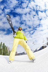 Cool young woman in mask standing and holding ski