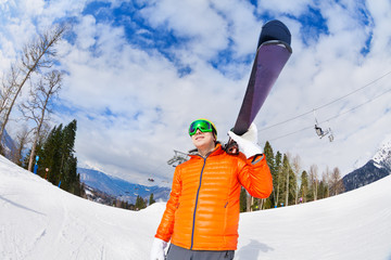 Happy young man wearing mask holds ski in winter