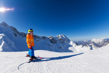 Boy skiing in sunny weather with mountain view