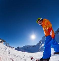 Fisheye view of smiling boy in ski mask skiing