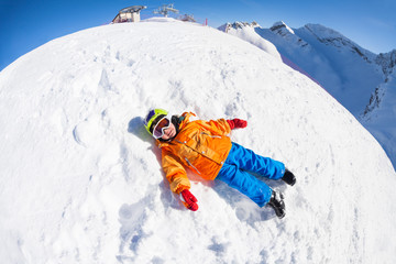 Fisheye view of smiling boy in mask laying on snow