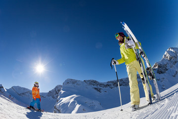 Small boy with woman in mask holding ski and poles