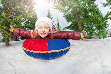Smiling girl on snow tube in winter during day