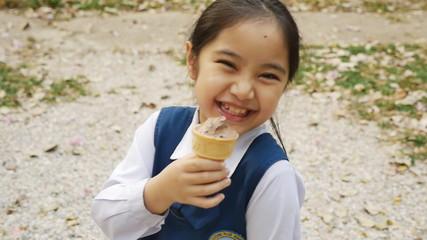 Slow motion of little Asian girl enjoying her ice cream