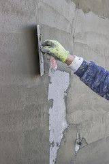 Worker's hand plastering a exterior wall
