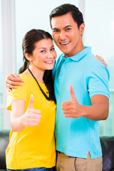 Young Asian couple in apartment with thumbs up