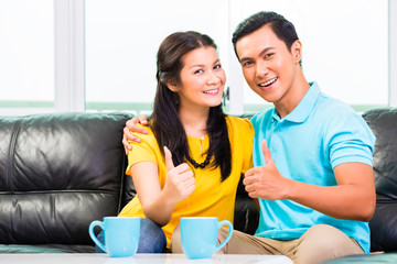 Young Asian couple on sofa or couch