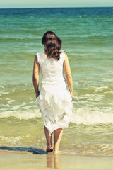 Young woman in white dress walking on the beach.
