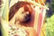 Young woman lying in a hammock in garden.