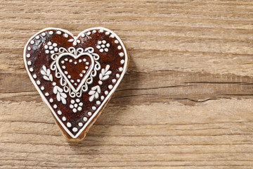 Gingerbread cookie in heart shape on a wooden background