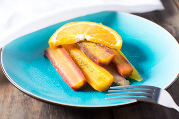 Plate of multi colored carrots with orange sauce