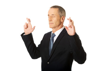 Businessman making a wish with fingers crossed