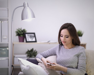Pretty girl using her smartphone on  couch at home in the living