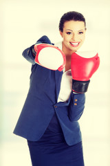 Young business woman wearing boxing gloves.