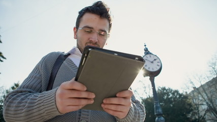 Businessman outdoors near a street clock looking at his watch