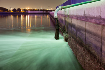 Sewage pipe discharging water into a river at night