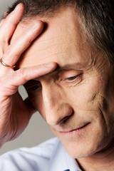 Depressed mature man touching his head