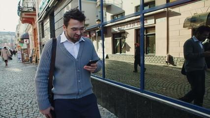 Young urban professional man using smart phone. Businessman