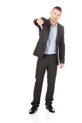 Young businessman gesturing thumbs down