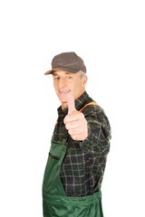 Mature gardener in uniform with thumbs up