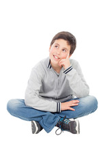 Pensive preteen boy sitting on the floor