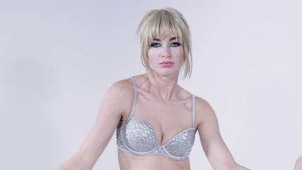 Cheerful blonde girl wearing diamond bra dancing in studio.