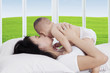 Attractive mother kissing her child on bed