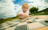 Fototapety Child playing draughts or checkers board game outdoor