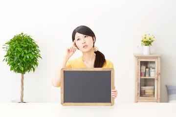メッセージボードを持って考える女性