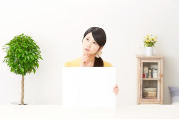 メッセージボードと考える女性