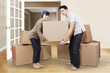 Couple unpacking cardboard in new home